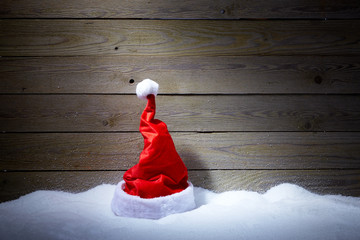 Santa hat in snow on wooden background 2