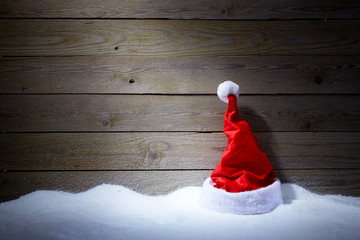 Santa hat in snow on wooden background