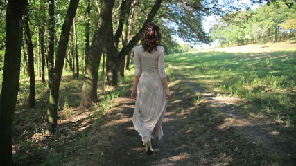woman in a light dress walking in a forest, park