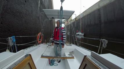 Senior captain on deck, sailboat ready to pass through lock