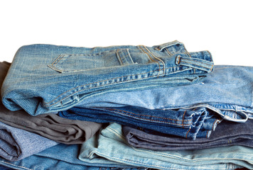 Pile of many colored jeans isolated on white background