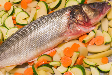 raw sea bass fish with sliced potatoes, carrots and zucchinis