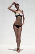 Beautiful tan female model posing in bikini and sunglasses. Agai