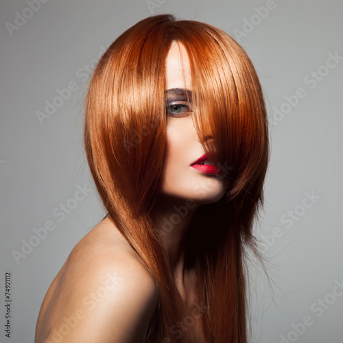 Beauty model with perfect long glossy red hair. Close-up portrai