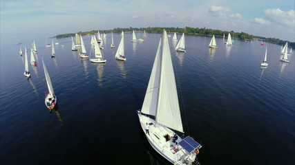 Numerous sailing yachts in open sea, regatta, competition, race