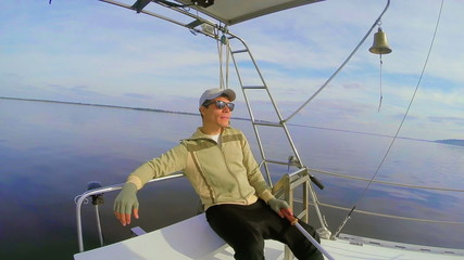 Confident young male having rest on sailing yacht open sea