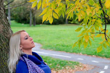 Beautiful blonde girl standing in the park on autumn day
