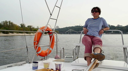 Young confident woman relaxing on sailing yacht, vacation, rest