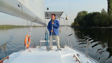 Happy handsome man rings bell on sailing yacht, active rest