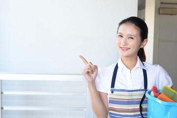 掃除道具を持つ笑顔の女性