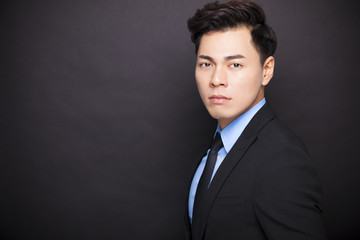 young businessman standing before black background