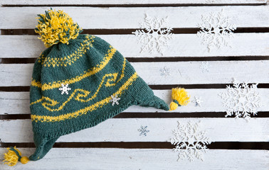 knitted hat and snowflake ornaments with a wooden background