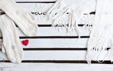 white mittens and scarf on a wooden plank background