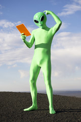 Confused Green Alien Man Scratching Head Holding Tablet