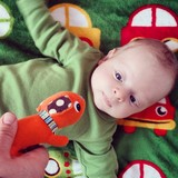 Green baby stimulation cuddly rattle poster