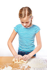 Girl kneads dough for pie on kitchen table isolated