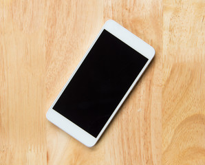 A white Smart phone on the wooden table