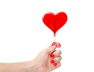 red heart shaped candy lollipop in hand