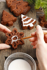 Decorating christmas gingerbread chocolate cookies with white ic