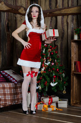 Beautiful woman in Santa Claus clothes near a Christmas tree wit