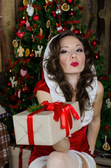 Beautiful woman in Santa Claus clothes near the Christmas tree