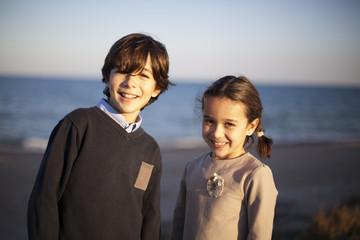 Niño y niña sonriendo frente al mar