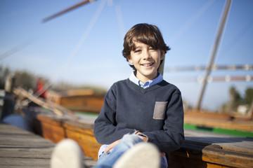 Niño sentado en embarcadero