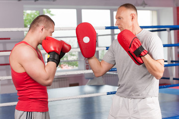 boxer and his coach doing some sparring in ring.