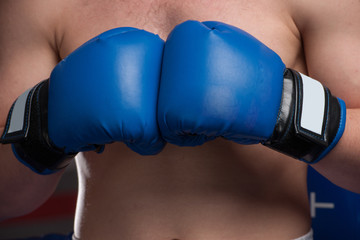 Boxer with blue gloves in dark room.