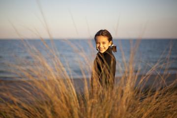 Niña con trenzas sonriendo frente al mar
