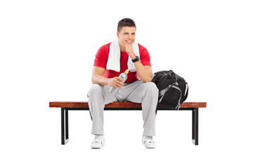 Handsome sportsman sitting on a wooden bench