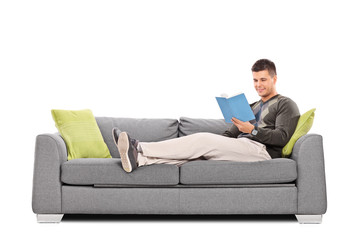 Relaxed young guy reading a book on a sofa