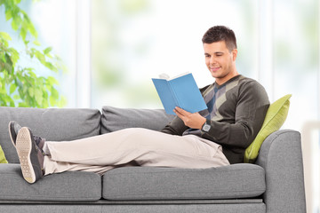 Young guy relaxing with a book at home