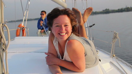 Happy woman lying on deck of sailboat, flirting with crew