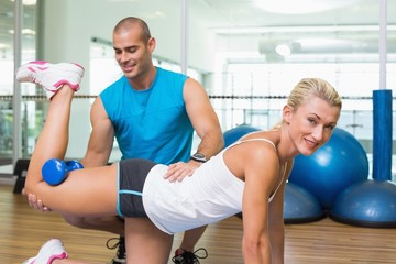 Trainer assisting woman with exercises at fitness studio