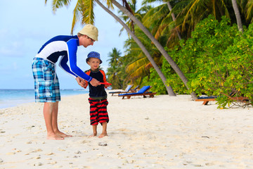 Father and son playing with flying disc at beach