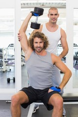 Trainer assisting young man with dumbbell in gym