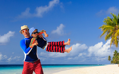 father and son playing on tropical beach
