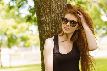 Beautiful young woman against tree in park
