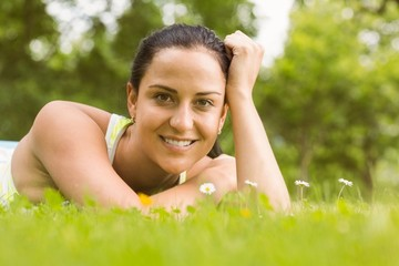 Cheerful fit brunette lying on the grass