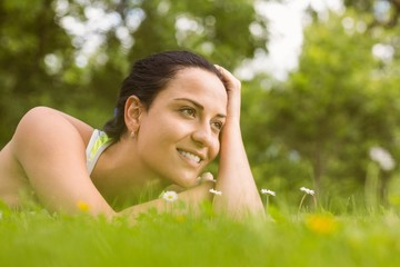 Relaxed fit brunette lying on grass