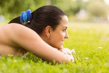 Happy fit brunette lying on the grass