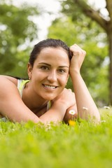 Smiling fit brunette lying on grass and looking at camera
