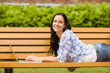 Casual brunette lying on bench typing on laptop