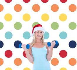 Composite image of festive fit blonde holding dumbbells