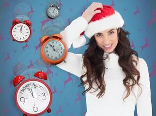 Composite image of confused brunette in santa hat