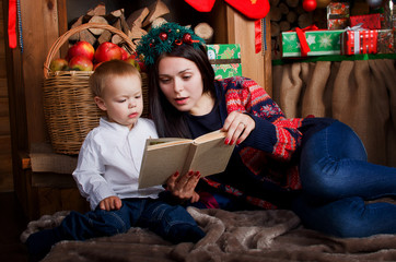 Mum with the son read fairy tales. Christmas Eve.