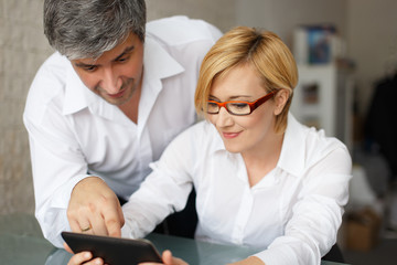 Businesspeople in office watching financial data on tablet