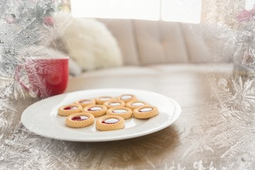 Composite image of cookies and mug on coffee table at christmas