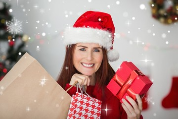 Composite image of festive redhead holding christmas gifts